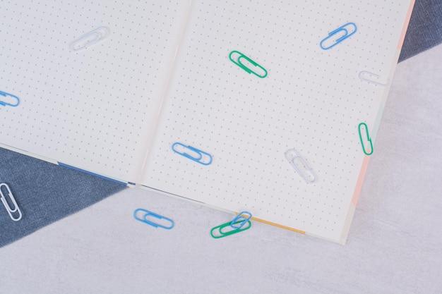 Des clips colorés éparpillés autour du cahier sur un tableau blanc.