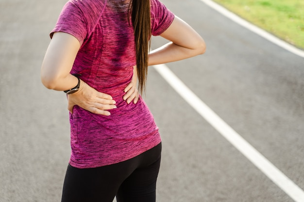 Cloaeup woman runner on running track touchant toucher le dos avec une blessure douloureuse