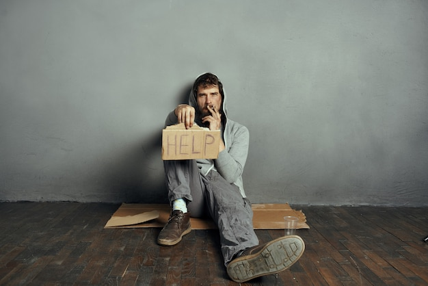 Le clochard barbu est assis sur le sol, tenant une pancarte, aide au mode de vie de la dépression