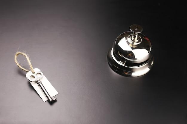 Cloche d'argent et la clé à la réception de l'hôtel sur fond noir