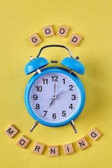 Cloche bleue et bonjour souhait. vue de dessus horloge vintage et bonjour fait de cubes en bois.