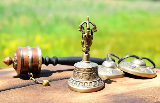 Cloche en cuivre avec objets religieux tibétains