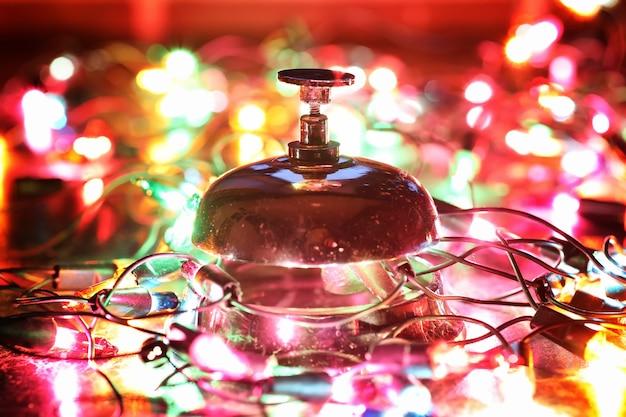 Cloche de réception sur la table et guirlande brillante de couleur sur fond