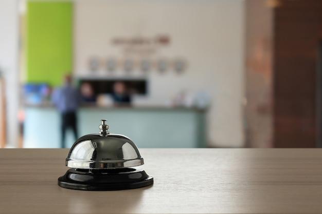 Cloche de service hôtelier sur comptoir en bois