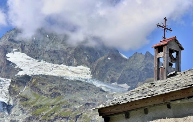 Cloche de la tour et croix d'une église dans un village alpin européen