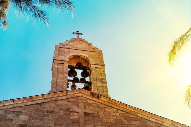 Clocher au sommet du toit de l'église grecque byzantine chrétienne orthodoxe. grande cloche en bronze, et une grande croix blanche, vue d'arrière-plan du ciel bleu nuageux sous le soleil jaune vif. espace de copie