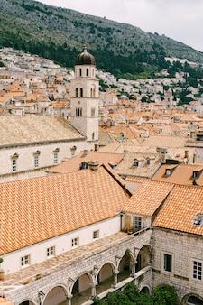Le clocher du monastère franciscain de dubrovnik dans la perspective des toits de la