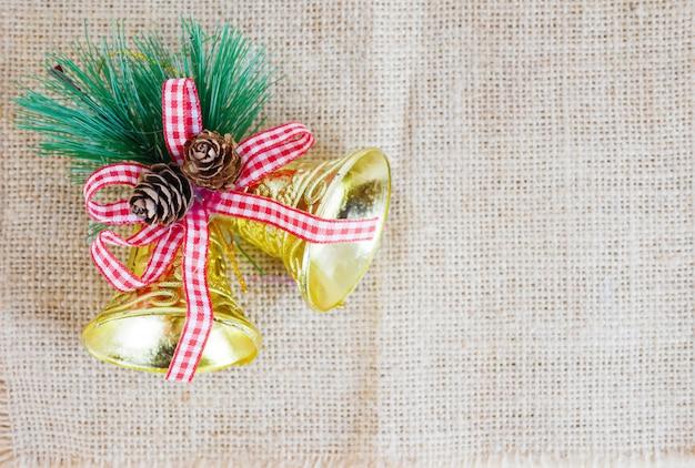 Cloches dorées noël avec ruban rouge et pins sur le sac