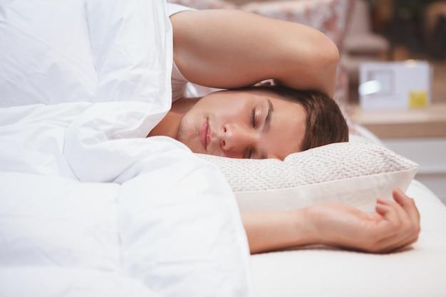 Cloe up d'un jeune homme endormi dans son lit