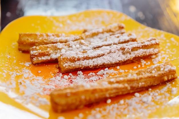 Cloes up churros garnis de sucre glace servi avec une sauce au nutella sur plaque jaune.