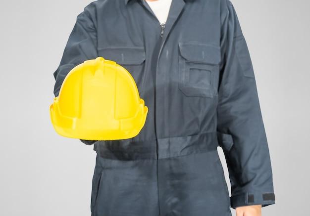 Cloes up worker debout en combinaison bleue tenant un casque jaune isolé sur fond gris