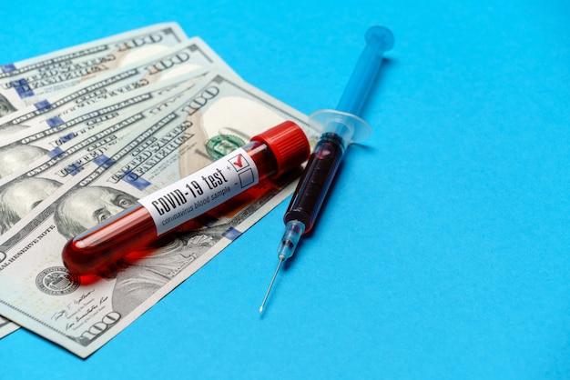 Close up 100 dollars américains et échantillon de sang en tube à essai sur bleu