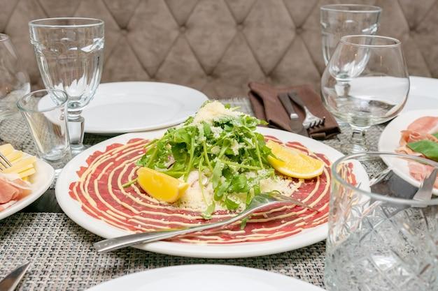 Close up d'antipasto italien - carpaccio à la roquette, parmesan et citron. apéritif méditerranéen.