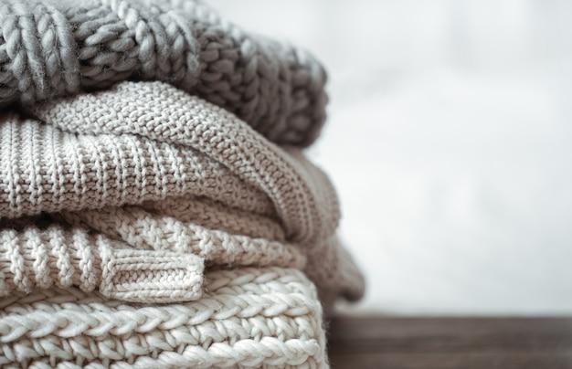 Close up d'articles tricotés soigneusement pliés de couleur pastel sur fond clair.