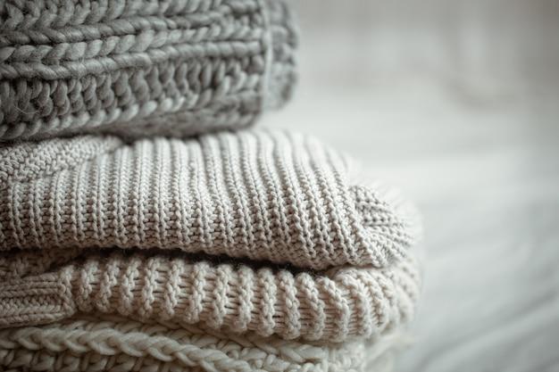 Close up d'articles tricotés soigneusement pliés de couleur pastel.