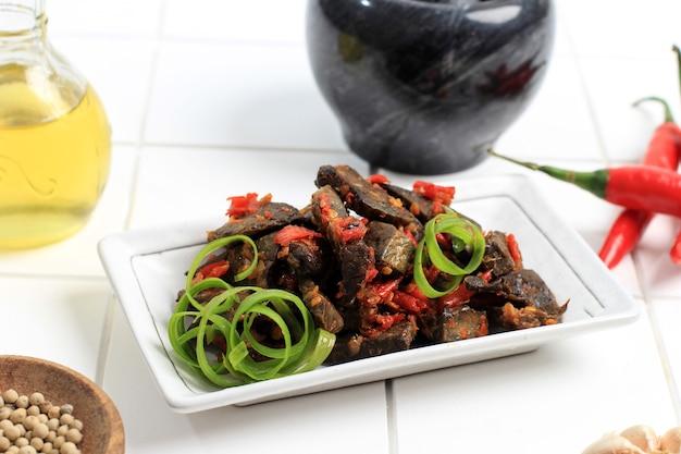 Close up balado paru, cuisine traditionnelle indonésienne à base de poumons de boeuf. cuit avec beaucoup de piment, d'ail, d'échalotes et de feuilles de citron vert. délicieux avec un goût épicé. espace de copie