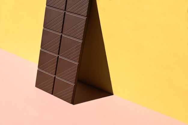 Close-up de barre de chocolat avec des ombres sur fond jaune et rose, conceptuel