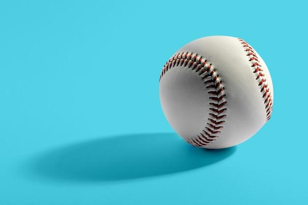 Close up de baseball en cuir de vachette unique avec coutures rouges sur fond bleu