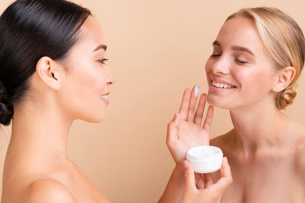 Close-up beaux modèles en utilisant la crème pour le visage