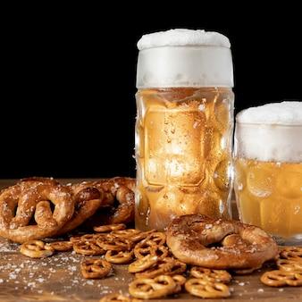 Close-up bière avec de la mousse et des bretzels