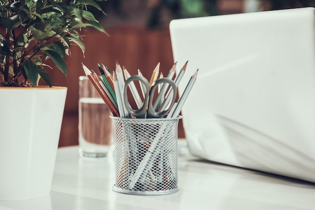 Close up bin avec des crayons et un ordinateur portable sur le bureau au bureau.