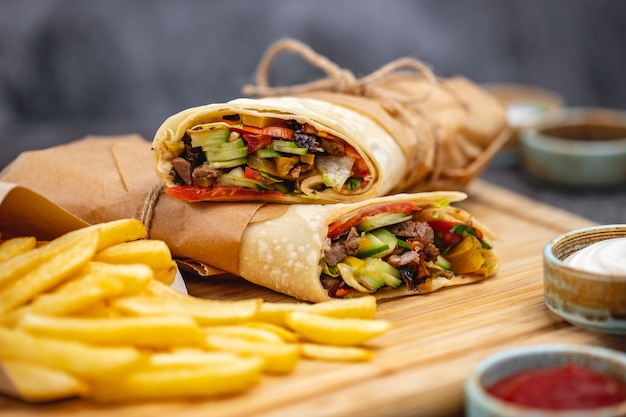 Close up de boeuf burrito avec tomate concombre laitue jalapeno servi avec frites et sauces