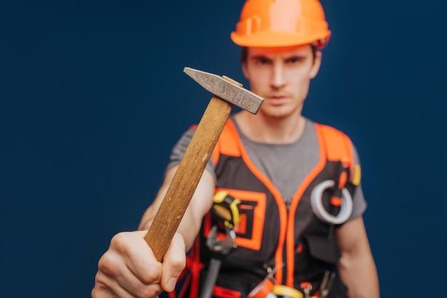 Close up builder dans un casque avec un marteau