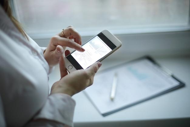 Close up.a business woman examine les données financières sur un smartphone.photo sur fond de bureau flou