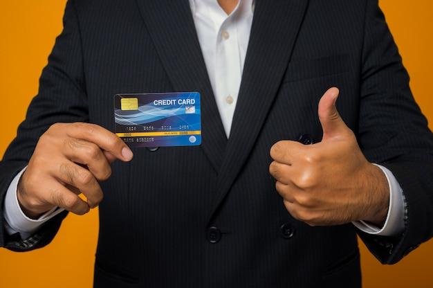 Close up businessman montrant la carte de crédit et obtenir le pouce vers le haut isolé sur jaune