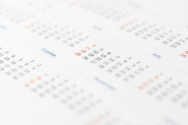 Close up calendrier page dates abstrait arrière-plan flou planification d'entreprise rendez-vous concept de réunion