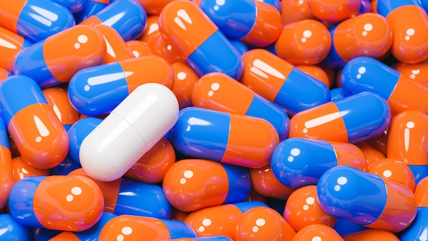 Close up de capsule de pilule blanche dans de nombreuses capsules de pilules orange et bleu