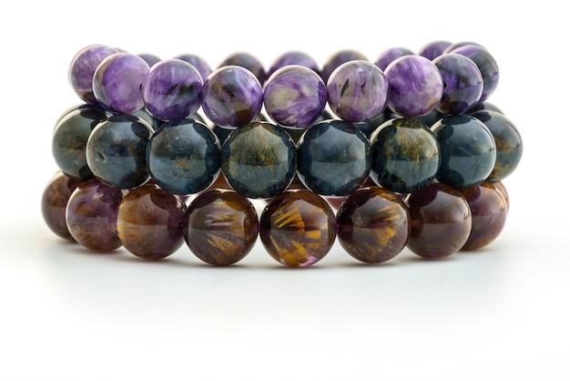 Close up charoid , pietersite et cacoxenite perles en bracelets sur fond blanc