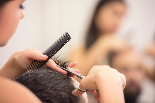 Close-up coiffeur avec des ciseaux et un peigne.