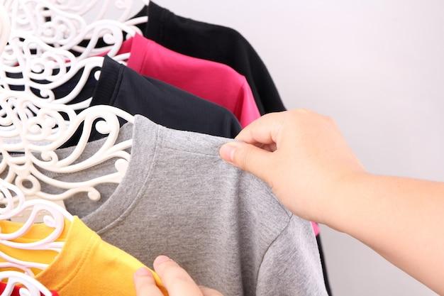 Close up collection de t-shirts colorés suspendus.