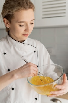 Close up cook en remuant les œufs
