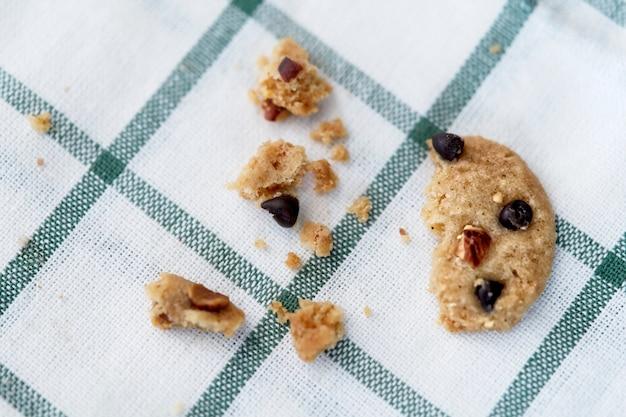 Close up cookie aux pépites de chocolat cassé sur une nappe à carreaux, cookie à moitié mangé