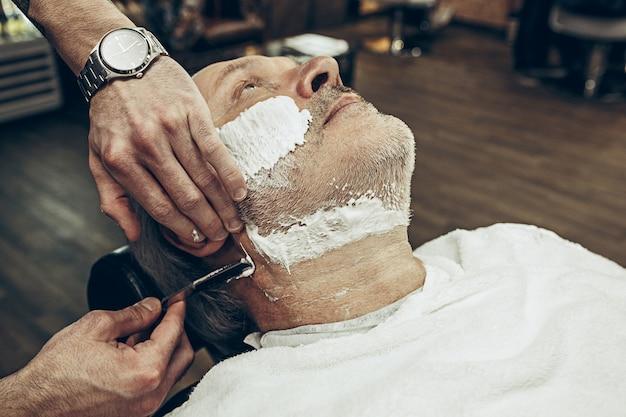Close-up côté vue de dessus bel homme caucasien barbu senior se toilettage de barbe dans un salon de coiffure moderne.