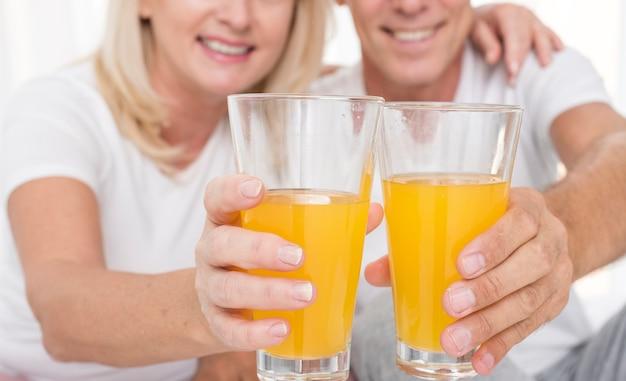 Close-up couple heureux avec des verres de jus