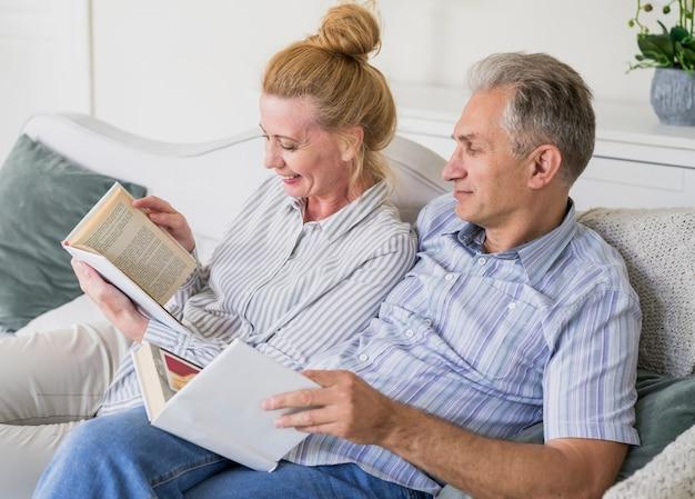 Close-up couple senior avec livre sur un canapé