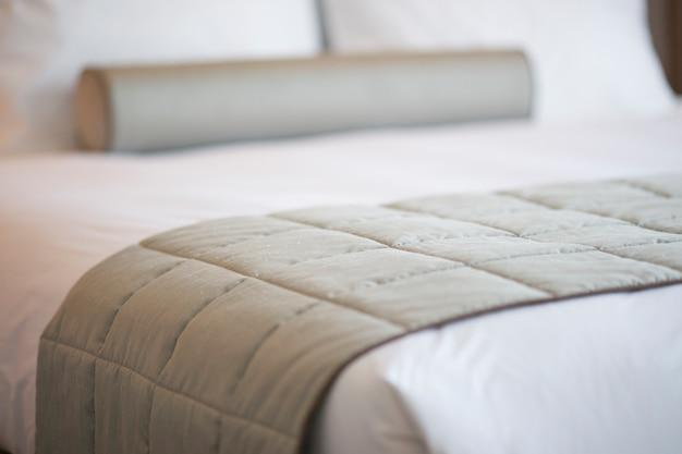 Close-up de la couverture grise sur le lit