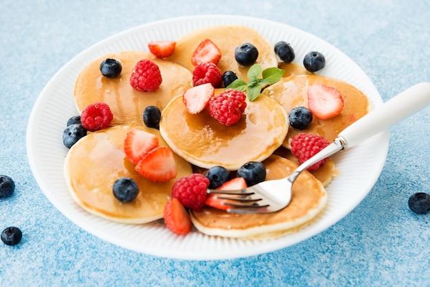 Close up de crêpes américaines avec du miel et des baies sur une assiette