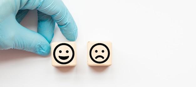 Close up custome choisir smiley et icône de visage triste sur cube de bois