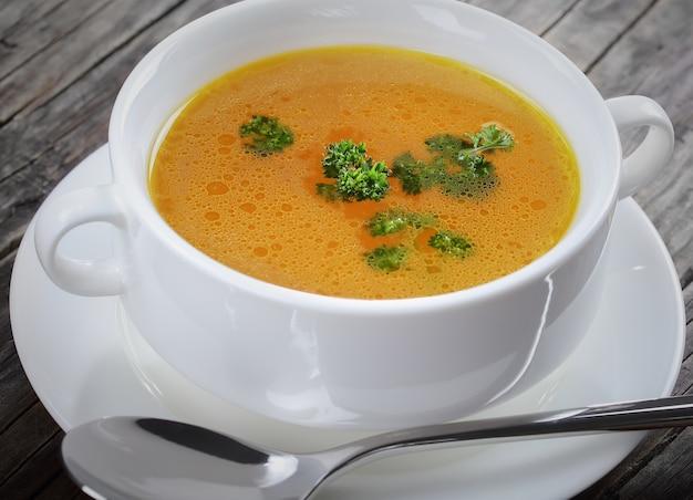 Close up de délicieux bouillon de poulet dans une tasse de soupe blanche avec cuillère
