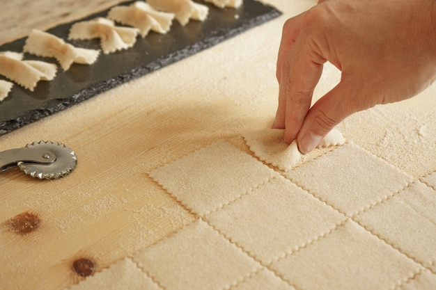 Close up detail du processus de pâtes farfalle maison. le cuisinier pétrit la pâte