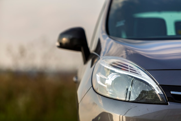 Close-up detail partie de voiture-phare noir brillant, miroir, capot et calandre sur fond extérieur flou. transport, prestige, concept de design moderne.