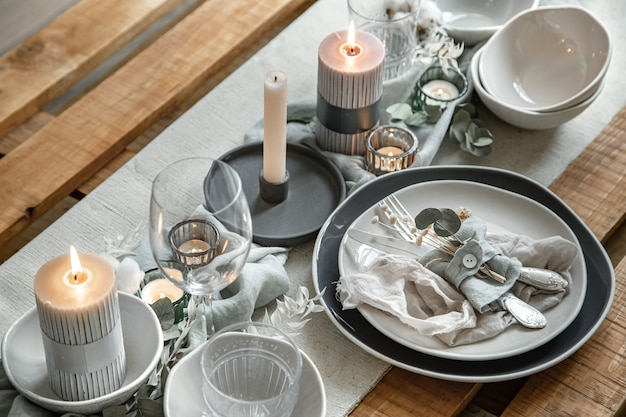 Close up detail d'une table de fête avec un ensemble de couverts, une assiette et des bougies en chandeliers