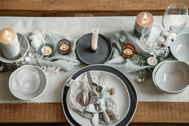 Close up detail d'une table de fête avec un ensemble de couverts, une assiette et des bougies en chandeliers.