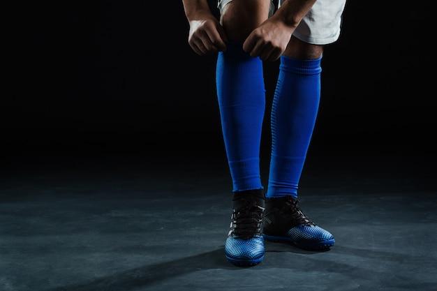Close-up du footballeur mettant sur sa chaussette