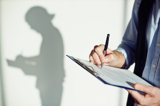 Close-up de l'écriture des employés sur un presse-papiers