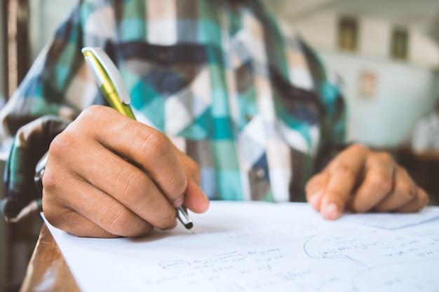 Close up les élèves qui écrivent et lisent les feuilles de réponses aux examens en classe d'école avec stress.